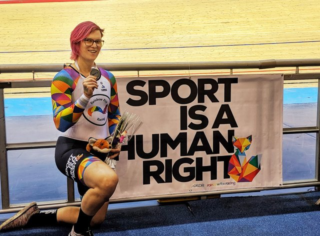 McKinnon poses proudly in front of a 'Sport is a human right' banner after defending her sprint title (Rachel McKinnon twitter)