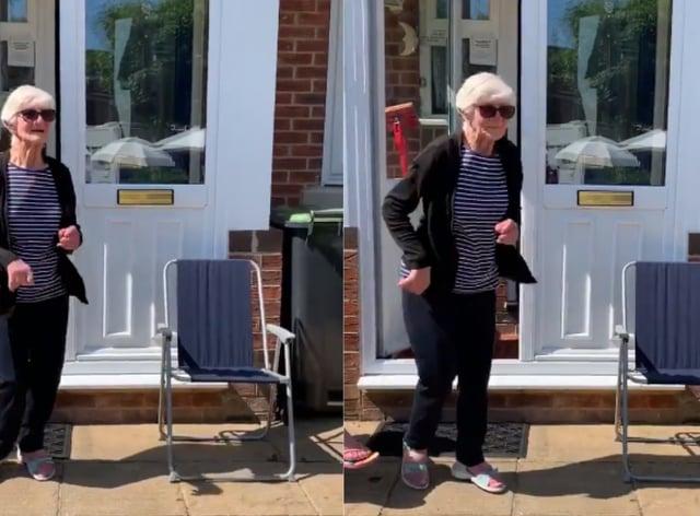 Woman dances in front of her door to celebrate VE Day
