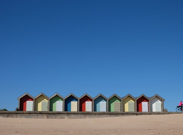 A clear blue sky over beach huts in Blyth, Northumberland