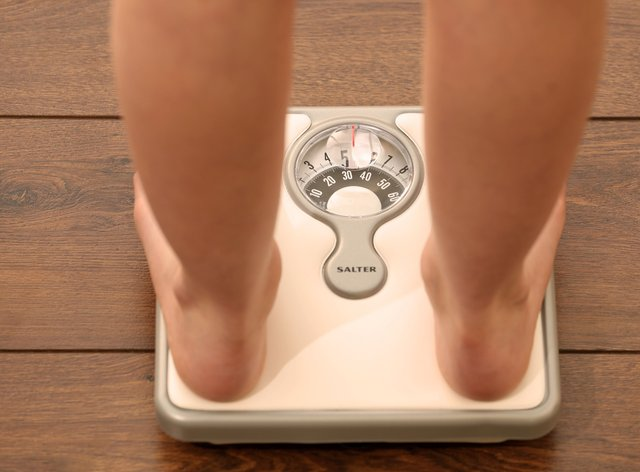 Someone weighing themselves on some scales