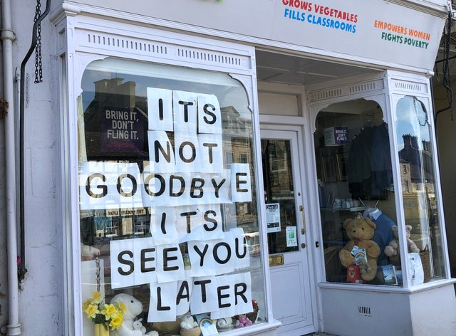 A sign in the window of an Oxfam shop