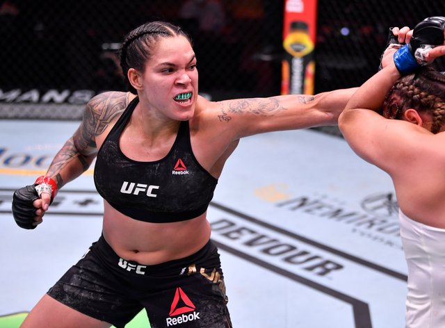 Amanda Nunes of Brazil punches Felicia Spencer of Canada in their UFC featherweight championship bout during UFC 250