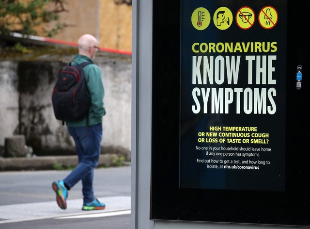 A person walks past an advertising board in Glasgow displaying a coronavirus-related message