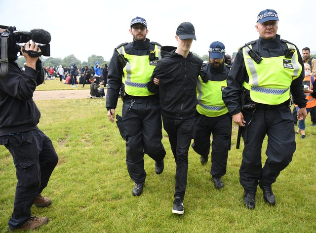 Police officers escort a man away from a Black Lives Matter protest rally in Hyde Park, London