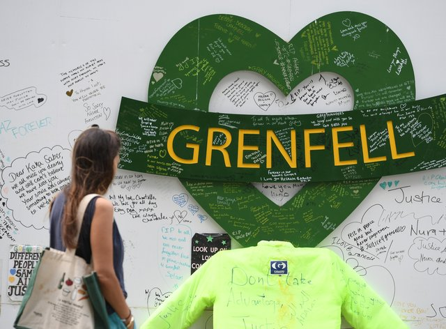 People at the Grenfell Memorial Community Mosaic at the base of the tower block in London on the third anniversary of the fire