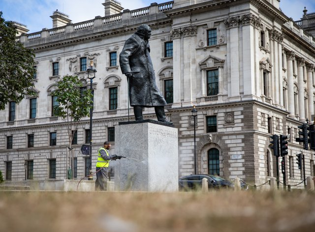 A worker cleans graffiti from the plinth of the statue of Sir Winston Churchill at Parliament Square in London