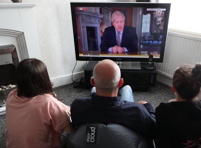 People watch Prime Minister Boris Johnson addressing the nation about coronavirus