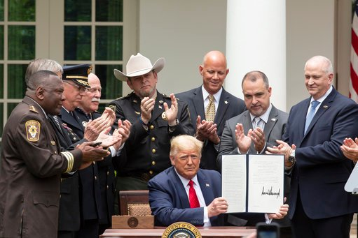 President Donald Trump displays an Executive Order on Safe Policing for Safe Communities after signing it in the Rose Garden of the White House