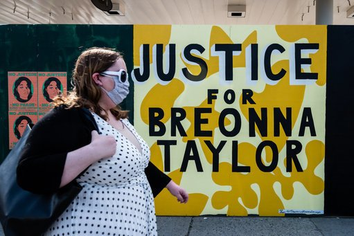 A woman walks past a mural by Theresa Rivera, which calls for justice for Breonna Taylor, in Brooklyn, New York