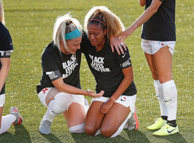 Julie Ertz puts and arm round Casey Short as they kneel together before Chicago's match against Washington