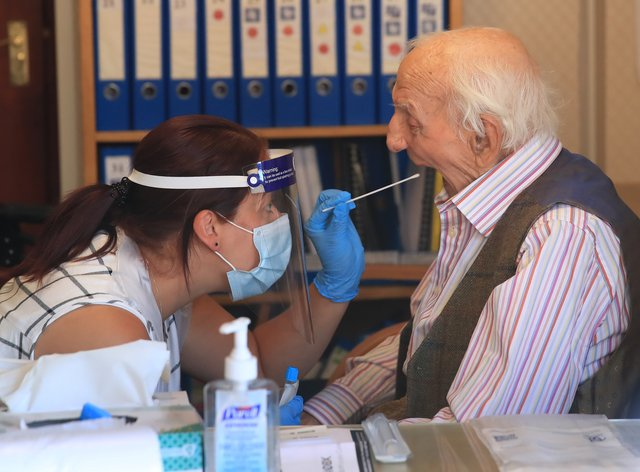 A care home resident undergoes a coronavirus swab test