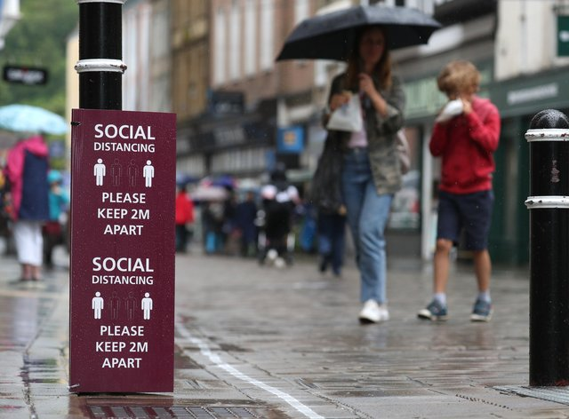 People walk past a social distancing sign as further coronavirus lockdown restrictions were lifted in England