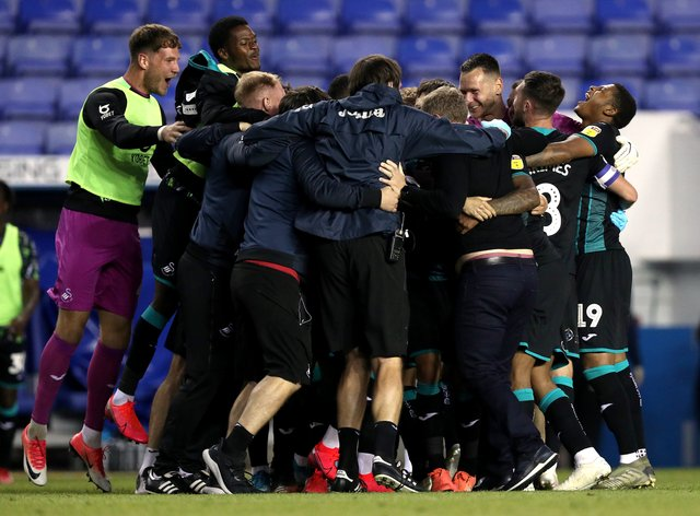 Swansea players celebrate reaching the play-offs after winning at Reading