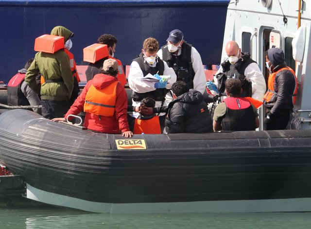A group of people thought to be migrants are brought into Dover, Kent