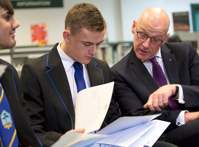 John Swinney with a pupil checking their results