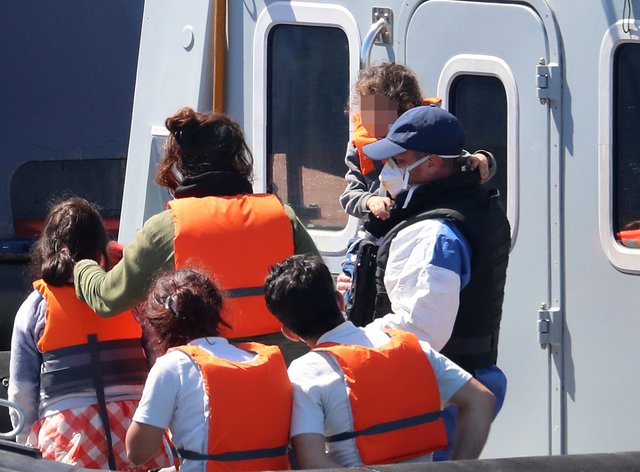 A Border Force officer escorts a young family thought to be migrants from a Border Force vessel
