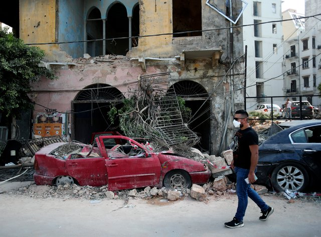 A man walks past a destroyed car in a neighbourhood near the scene of Tuesday's explosion in Beirut, Lebanon