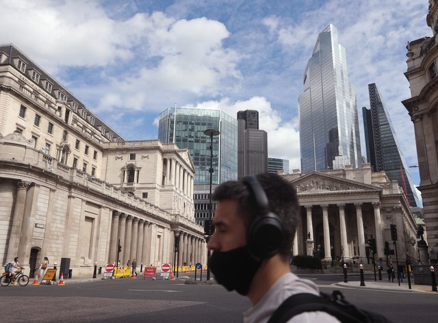 A man wearing a face mask walks past the Bank of England