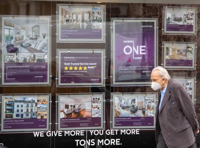 A man walks past an estate agent's window