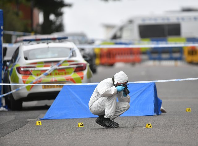 A police forensics officer taking photographs in Irving Street in Birmingham after a number of people were stabbed in the city centre