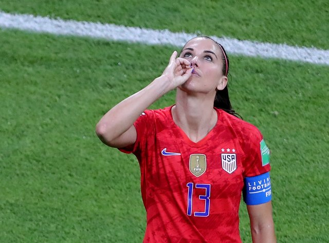 Morgan made a tea-drinking gesture as she celebrated scoring against England last year (Richard Sellers/PA).