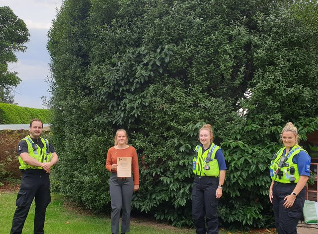 Naomi Jupp receives her award from Dorset Police neighbourhood officers (Dorset Police/PA)