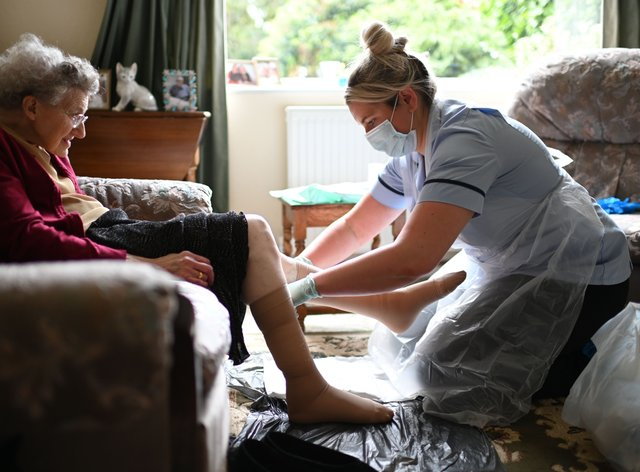 A seated care home resident is assisted by a health worker