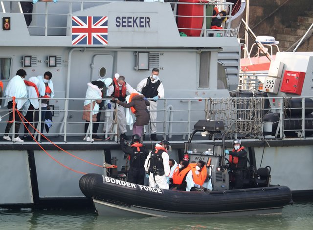 A group of people, thought to be migrants, disembark the deck of HMC Seeker at Dover marina