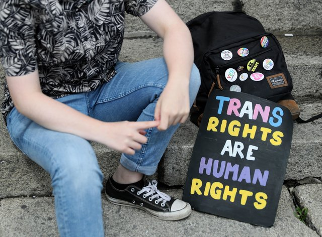 A person with a trans rights sign