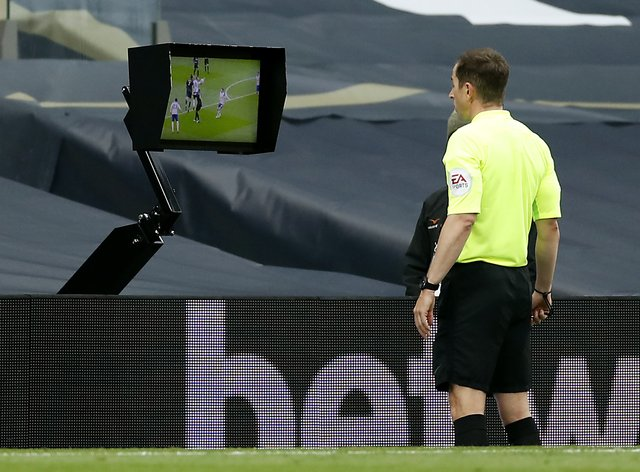 Referee Peter Bankes watched the late incident at Tottenham back on a pitchside monitor (Andrew Boyers/PA).