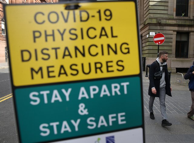 Members of the public walk past social distance signs
