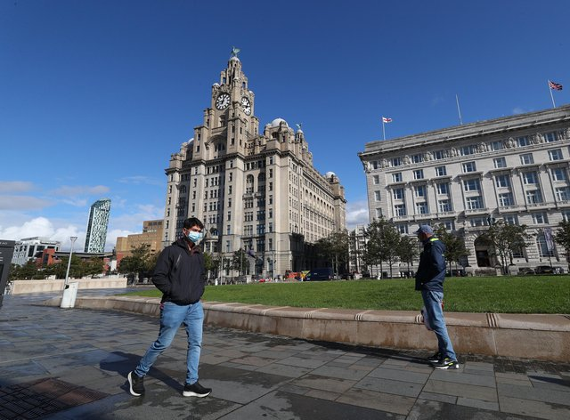 A man in a face mask walks past the Liver Building in Liverpool