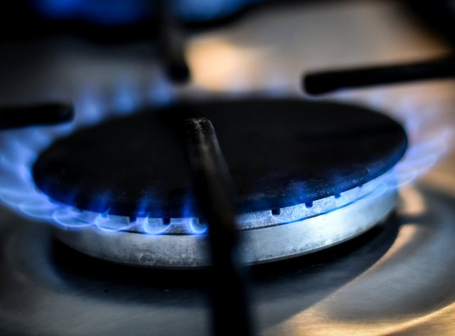 A lit gas ring on a domestic hob