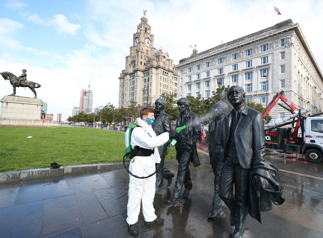 A worker spray cleans a Beatles statue in Liverpool (Peter Byrne/PA)