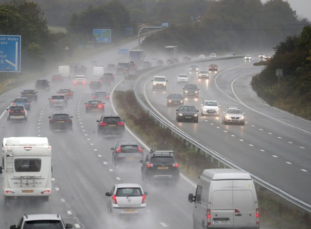 Cars make their way along the M4 motorway as heavy rain lashes the UK