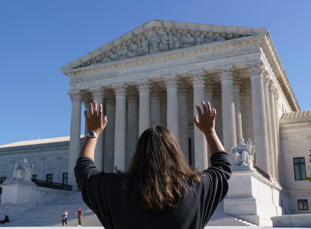 Megan Bixler of Tyler, Texas, holds out her hands in prayer as she and others from a Christian group, Youth With a Mission, sing at the Supreme Court in Washington, (J. Scott Applewhite/PA)