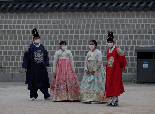 """Visitors dressed in South Korean traditional """"Hanbok"""" attire, wearing face masks as a precaution against the coronavirus, stand at the Gyeongbok Palace, one of South Korea's well-known landmarks, in Seoul, South Korea (Lee Jin-man/AP)"""