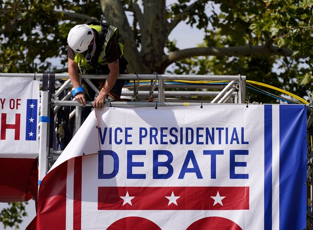 A worker hangs a banner as preparations take place for the vice presidential debate outside Kingsbury Hall at the University of Utah
