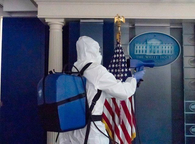A member of the cleaning staff sprays The James Brady Briefing Room of the White House