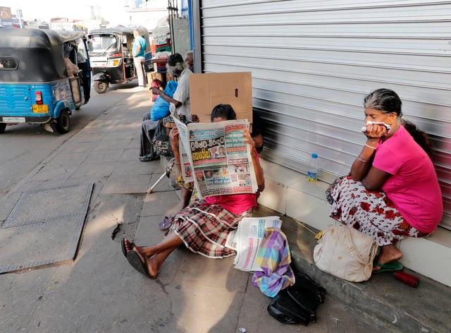 A Sri Lankan woman covers her face (Eranga Jayawardena/AP)