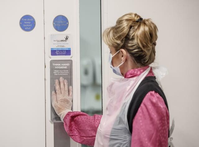 Vida Grange employee Debs Bannister uses a Surfaceskins self-disinfecting door pad at the Vida Grange care home in Harrogate
