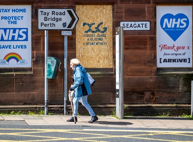A woman passes posters supporting the NHS