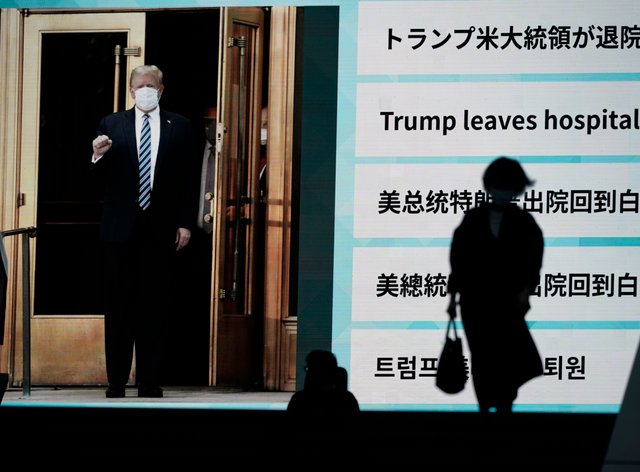 People in Tokyo walk past a screen showing the news report that President Donald Trump has left hospital