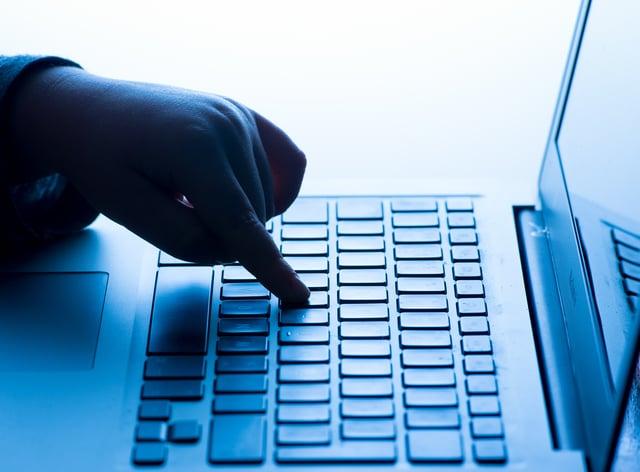 A child's hand presses a key of a laptop keyboard (Dominic Lipinski/PA)