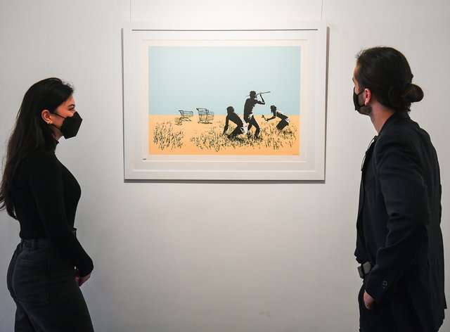 Gallery assistants look at a limited edition print of Trolleys (Colour) (2007) by Banksy, a part of the Catch Me If You Can exhibition