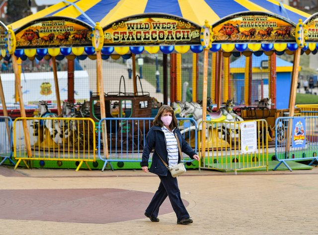 A masked woman walks past closed fairground rides on the seafront at Barry Island in the Vale of Glamorgan