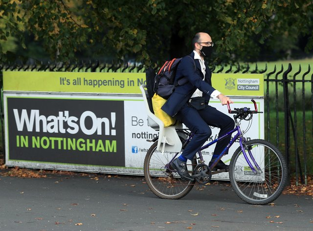 A man wearing a face covering cycling in Nottingham
