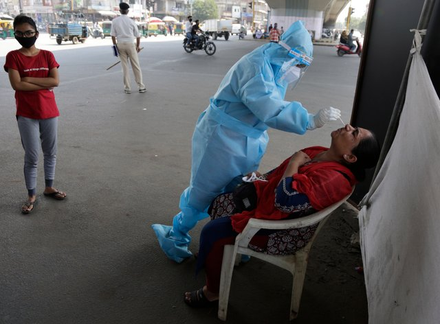 A health worker takes a nasal swab sample to test for Covid-19 by a roadside in Ahmedabad, India (Ajit Solanki/AP)
