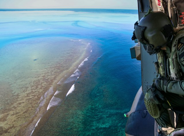 Leading Seaman Daniel Atkins looks out over Elizabeth Reef in search of unexploded ordnance