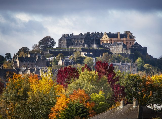 Stirling Castle surrounded by trees displaying their autumn colours